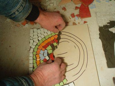 На покрытую клеем поверхность складываются кусочки мозаики